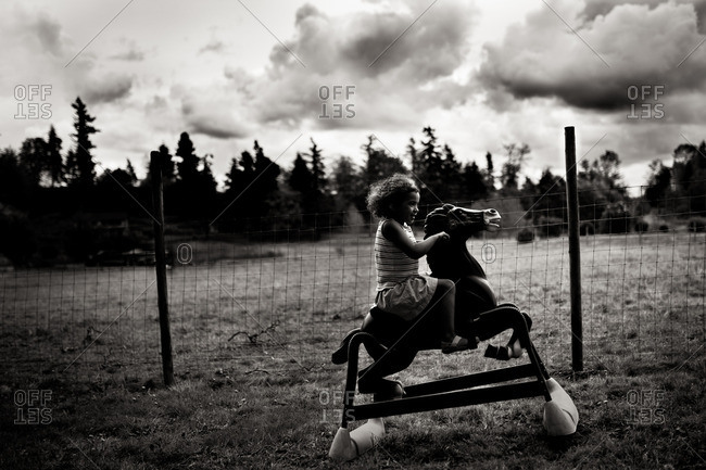 Girl riding rocking horse in field