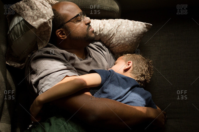 Boy lying with man napping on couch