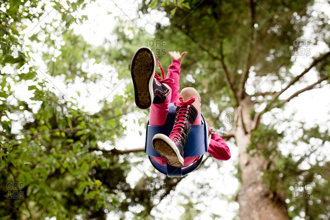 Girl in high top shoes on tree swing