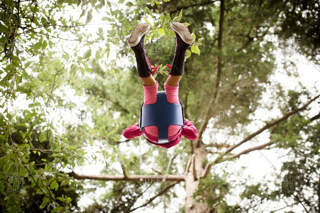 Girl in canvas boots on tree swing