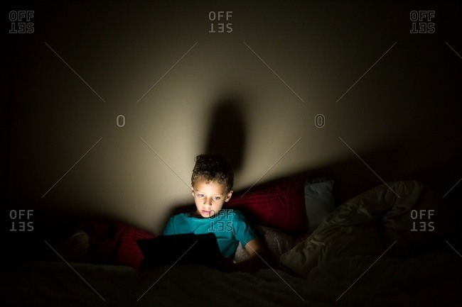 Mixed race boy using tablet in bed