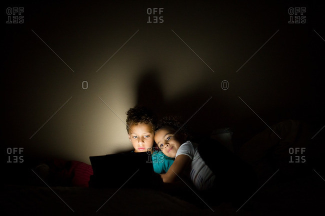 Mixed race siblings watching tablet in bed
