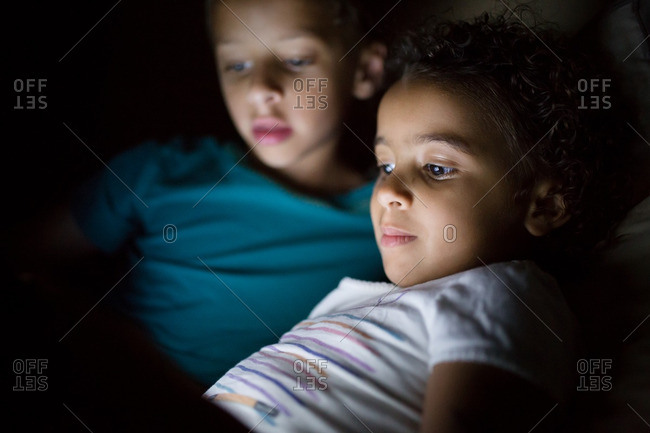 Siblings watching a tablet in bed