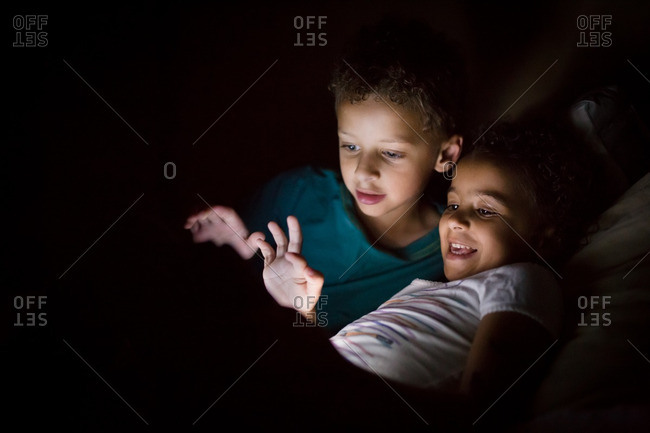 Two kids in light from a tablet