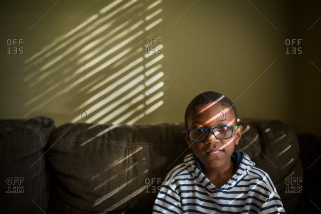 African American boy on couch in sunlight