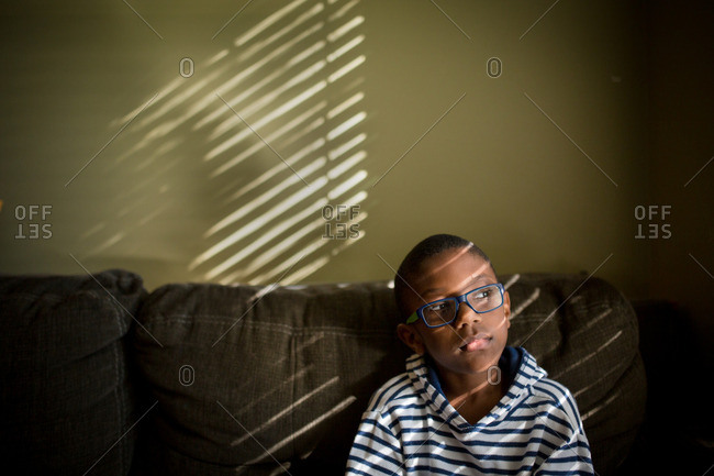 Pensive boy on couch in sunlight