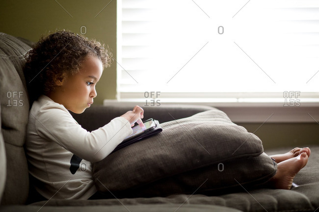 Biracial girl using tablet on couch