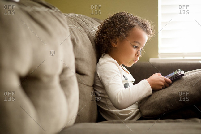 Biracial girl watching tablet on couch