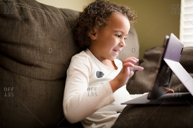 Girl having fun with tablet on couch