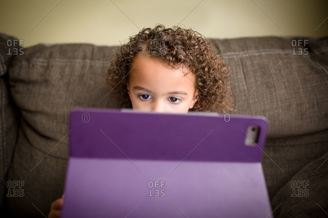 Girl focusing on tablet on couch