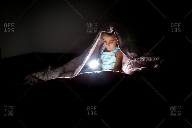 Girl reading in bed with flashlight