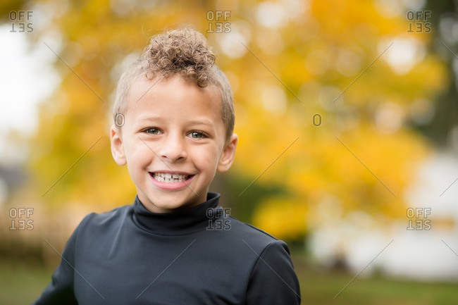 Smiling biracial boy in fall setting