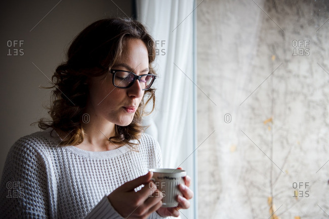 Woman blowing on a warm cup of coffee