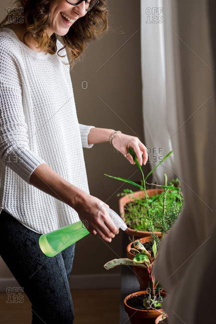 Happy woman watering plants by a window