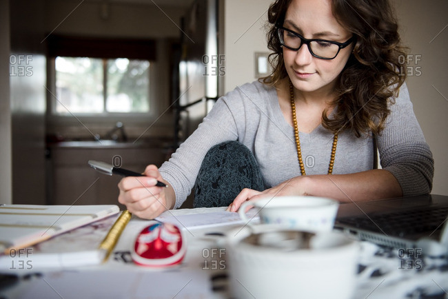 Woman writing down a recipe on a note card