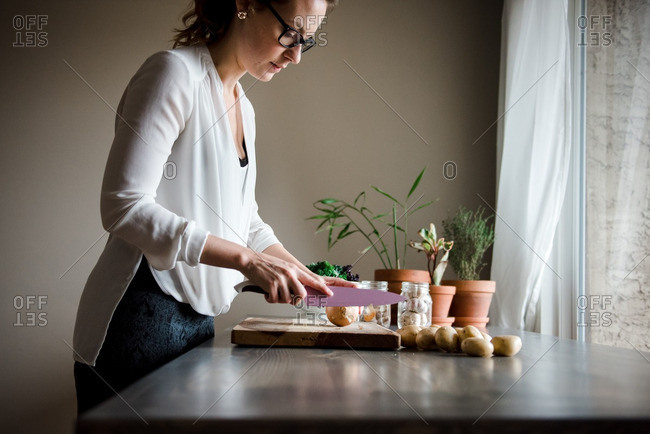 Woman slicing onion on a wooden cutting board