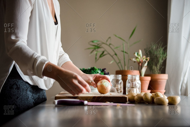 Woman cutting onion on a wooden cutting board
