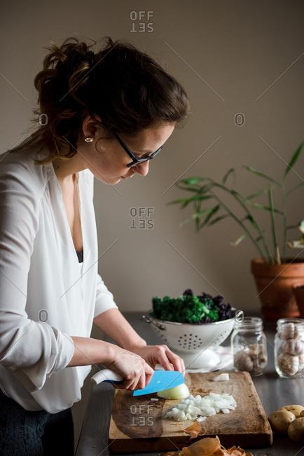 Woman chopping onion on a wooden cutting board