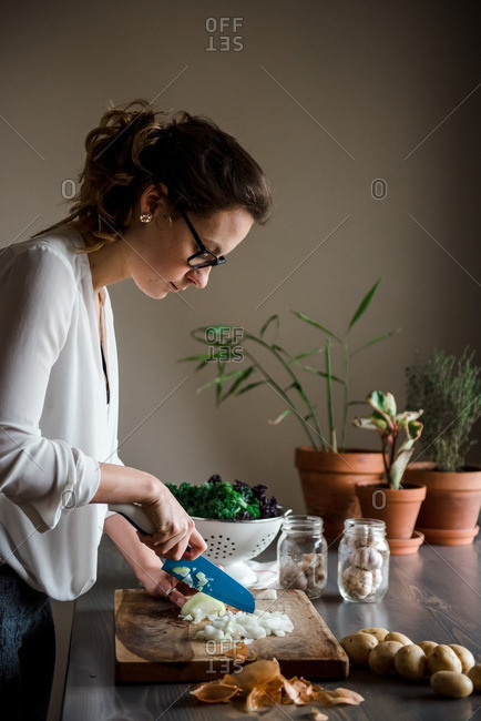 Woman dicing onion on a wooden cutting board