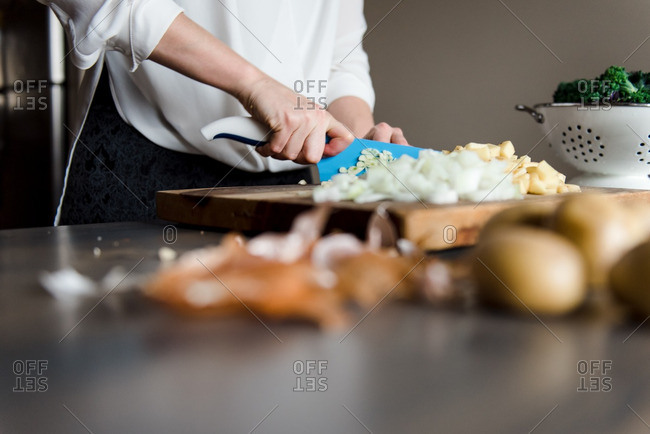 Woman dicing vegetables on a wooden cutting board