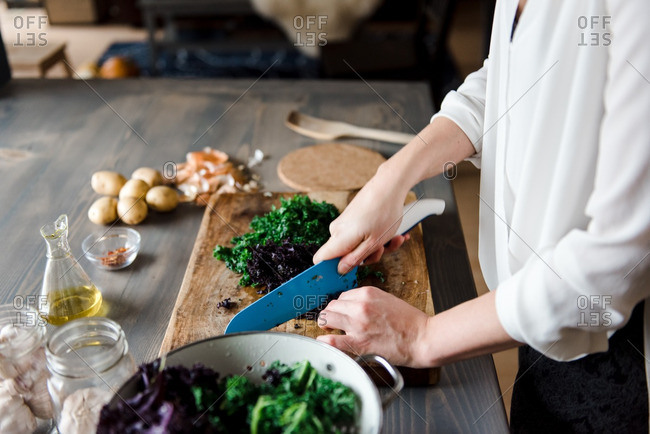 Woman chopping kale on a wooden cutting board