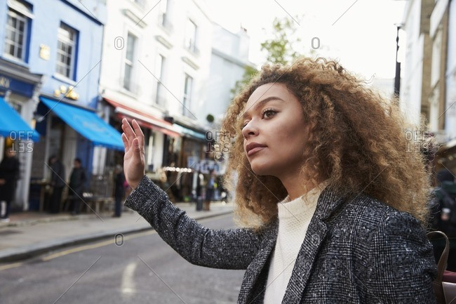 Stylish young woman hailing taxi on busy city street