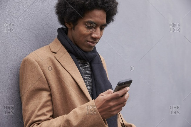 Man leaning against wall using mobile phone on city street