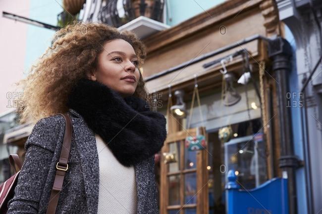 Stylish young woman walking along busy city street