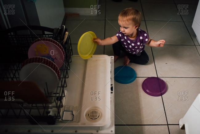 Toddler girl playing by dishwasher