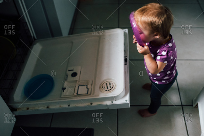 Toddler with plastic plate by dishwasher