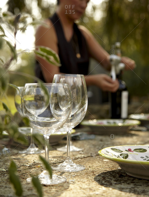 Wine glasses and woman opening wine for outdoor dinner party