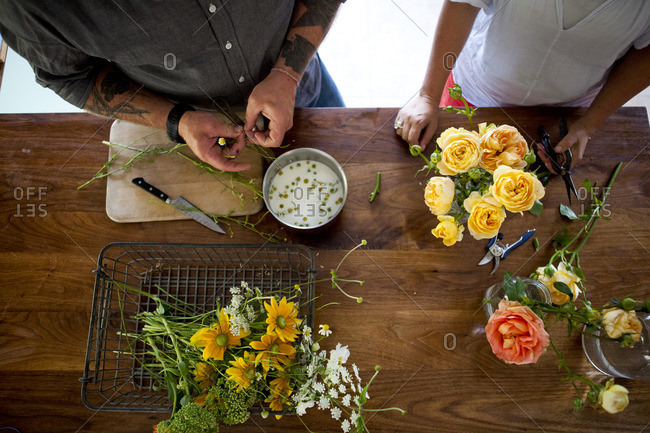 Man and woman cutting and separating flowers