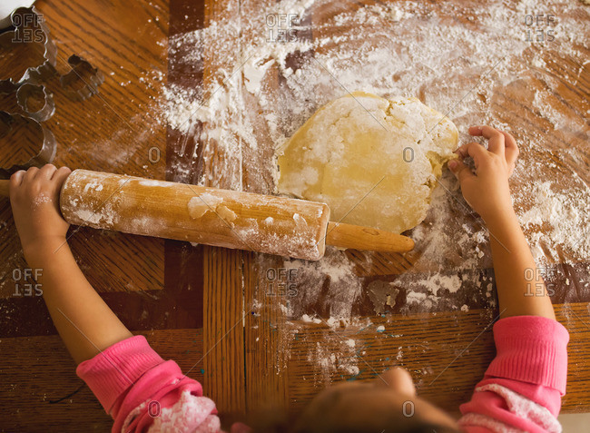 Girl rolling out dough on table