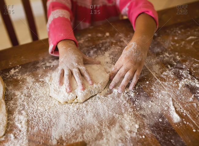 Girl's hands by raw dough