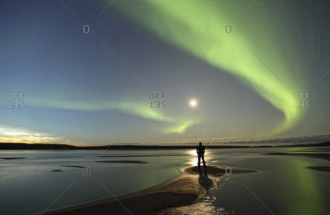 Person standing along the shores of the MacKenzie River with the aurora borealis overhead, Northwest Territories, Canada.