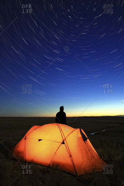 Person stargazing with his tent lit up at night overlooking the Frenchman River Valley, Grasslands National Park, Saskatchewan. A hint of aurora borealis can be seen on the horizon. Timed exposure to get star trails.