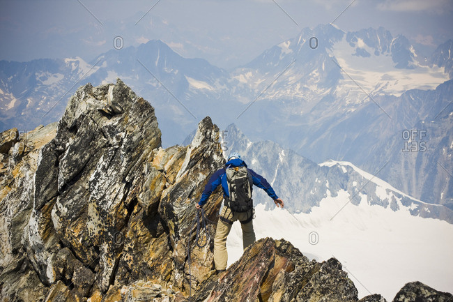 A young man mountain climbing the classic north west ridge of Mt. Sir Donald, Glacier National Park, British Columbia, Canada