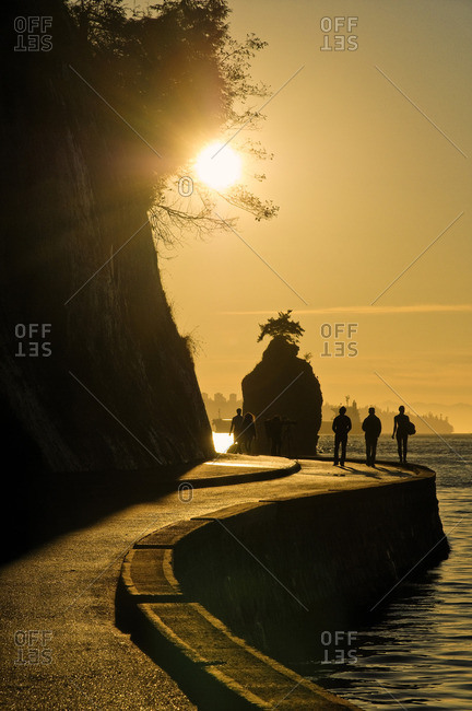 Sunset silhouettes Siwash Rock, with people on the  Stanley Park seawall, Vancouver, British Columbia Canada