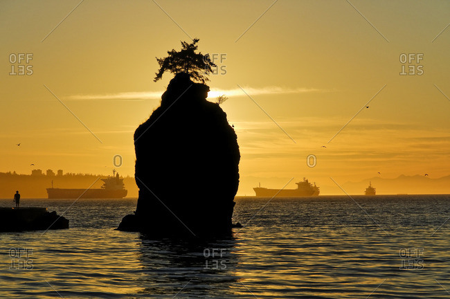 Sunset silhouettes Siwash Rock, the seawall, Stanley Park, Vancouver, British Columbia Canada