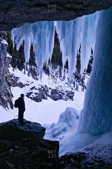 Hiker dwarfed by giant icicles, behind Panther Falls in Winter,  Banff National Park, Alberta, Canada