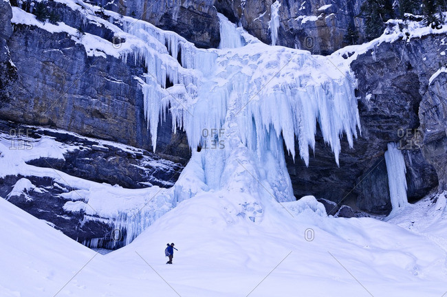 Photographer dwarfed by frozen Panther Falls in Winter,  Banff National Park, Alberta, Canada