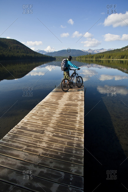 A male mountain biker enjoys a peaceful  moment in the morning before an all day ride in Spruce Lake Protected Area, Southern Chilcotins, British Columbia, Canada