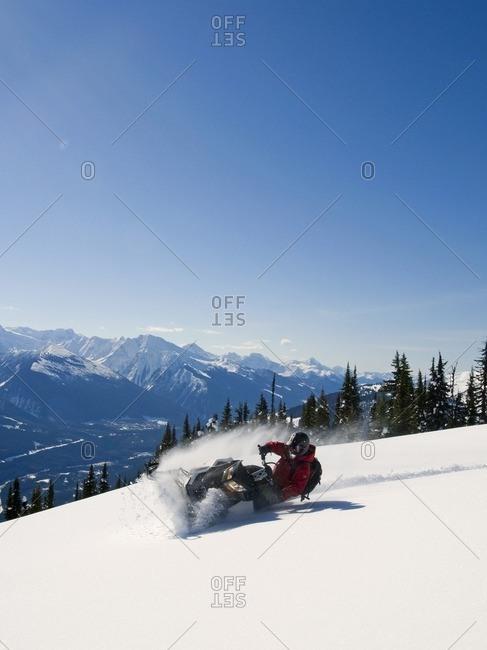 A snowmobiler takes advantage of a blue bird day and carves a tight turn in the powder in the Monashee mountain range, near Valemount, Thompson Okanagan region, British Columbia, Canada