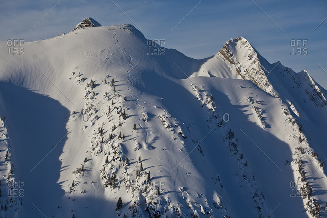 A backcountry snowboarder rides a steep line in the Kicking Horse Backcountry, Golden, British Columbia, Canada