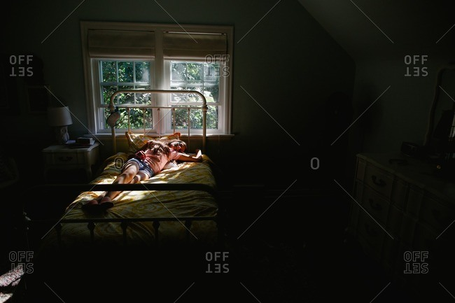 Tween girl on her bed in contrasting light