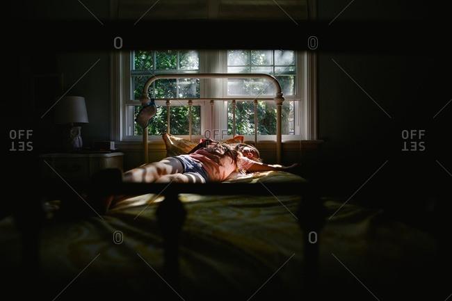 Tween girl sleeping on her bed in contrasting light