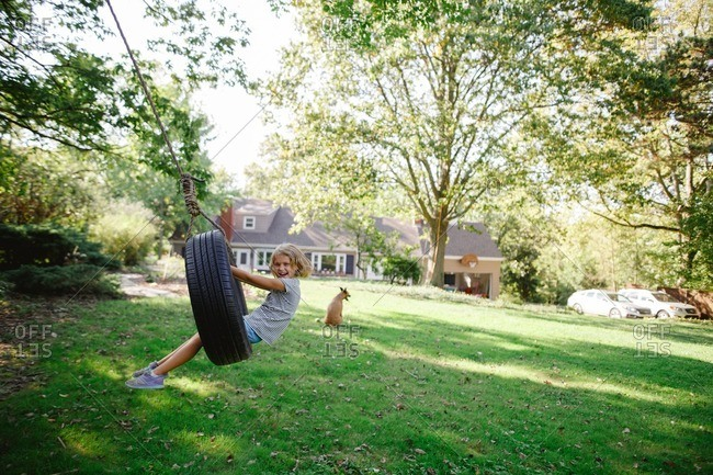 Young girl swinging on a tire swing in her backyard