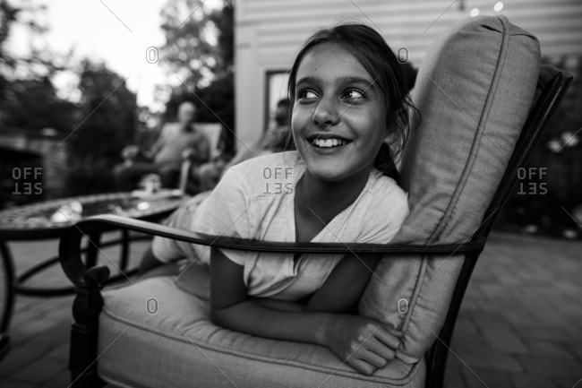 Tween girl sitting on patio furniture