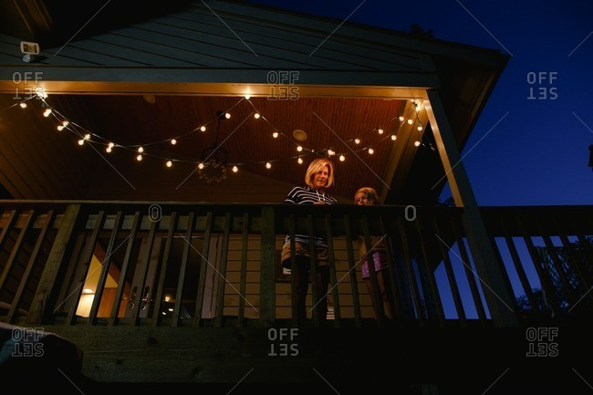 Little girl with grandma on a deck with lights
