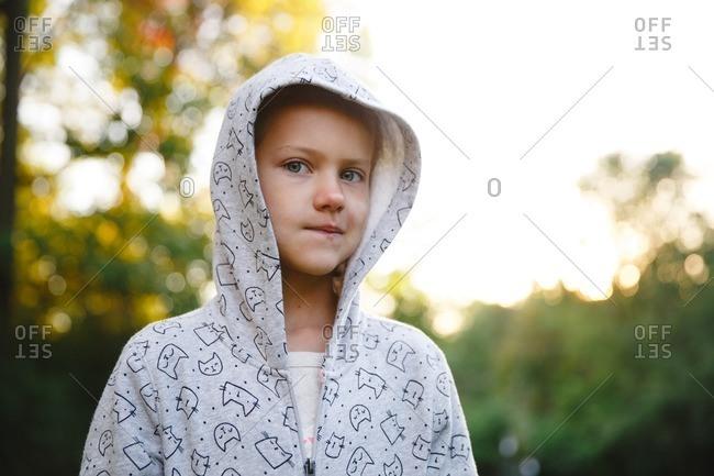 Little girl wearing hooded sweatshirt with cats on it